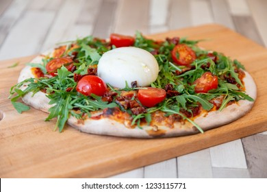 a pizza on a wooden board with cherry tomatoes, arugula, and burrata cheese on a wooden table