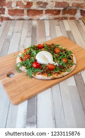 A pizza on a wooden board with cherry tomatoes, arugula, and burrata creamy cheese on a wooden table and brick wall for background