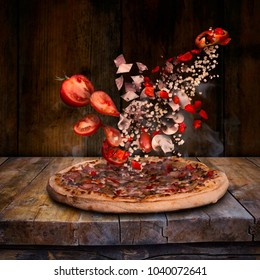 Pizza on a wooden board, and the ingredients falling