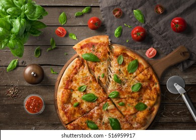 Pizza on wooden board, with tomatoes and basil, Italian style on old wooden table, top view.