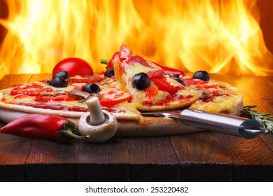 Pizza on wooden table with one slice on a lifter, real oven fire on background