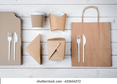 Pizza, paper bag, sandwich box, French fries container, plastic cutlery and take-out coffee cup, top-view. White wooden background. Food delivery.
