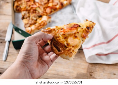 pizza in paper box on wooden background