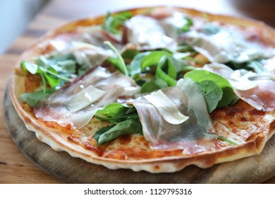 Pizza with parma ham salad rocket on tomato sauce with wood table background