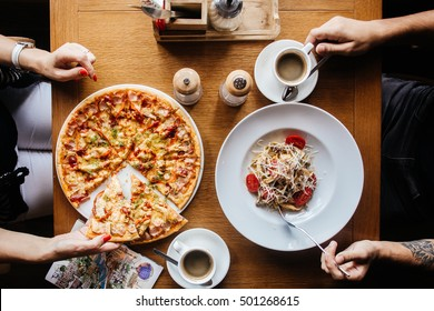 Pizza and pasta on a table with hands