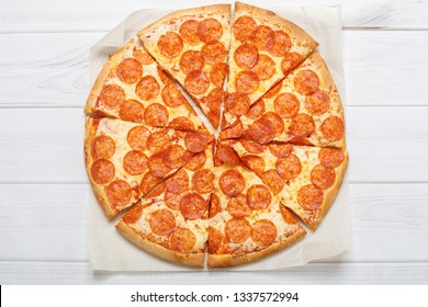 Pizza peperoni in light wooden background.