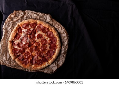 pizza peperoni on black stone background