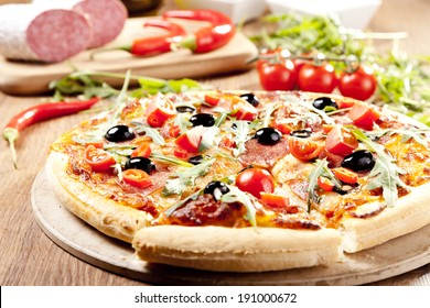 Pizza peperoni on plate with black olives, rocket and mozzarella cheese