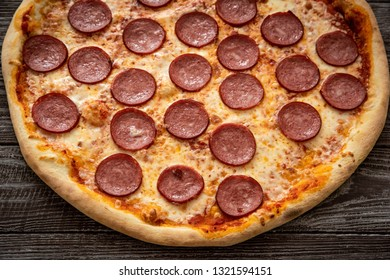 Pizza pepperoni on wooden table close up