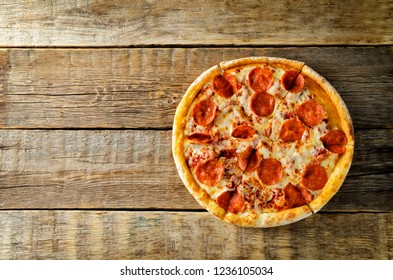 Pizza with pepperoni, tomato sauce and cheese on a wood background. toning. selective focus