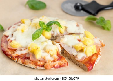 Pizza with pita crust, pinepapple and ham topping with fresh basil on top