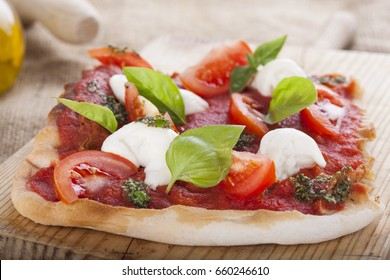 pizza pomodoro, vegetarian and homemade with mozzarella, tomatoes and basil isolated on background