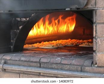 pizza prepares in old stove near fire