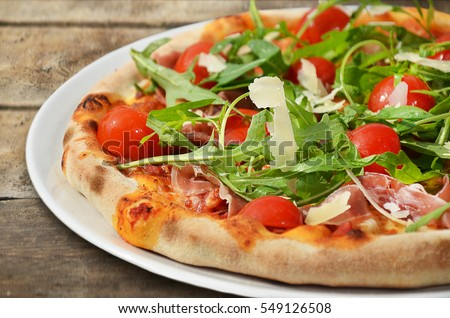 Pizza with prosciutto and rocket salad on wooden table.