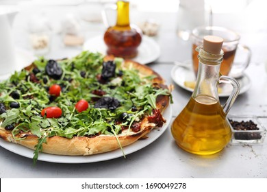 Pizza with prune, goat cheese, arugula and tomatoes. Tasty delicious pizza.