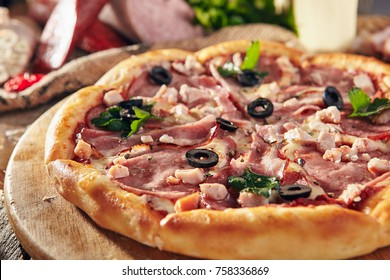 Pizza Restaurant Menu - Delicious Fresh Meat Pizza with Bacon, Sausage and Chicken. Pizza on Rustic Wooden Table with Ingredients.