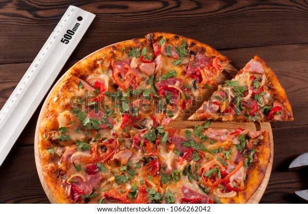 Pizza with a ruler on a wooden background. The concept of fair control of portion size