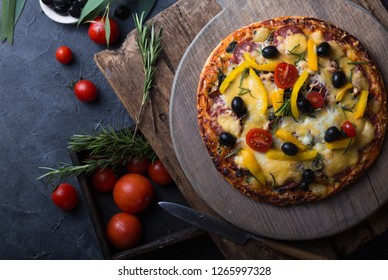 Pizza with salami, mozzarella, black olives, spices, tomato fresh rosemary. Italian Dark stone background.