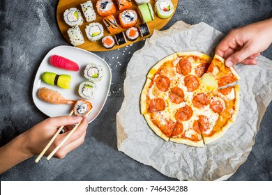 Pizza with salami, set of sushi rolls and hands take food. Food background. Flat lay, top view.