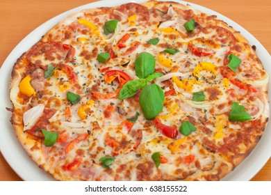Pizza with salami and vegetables. (Color toned image)
