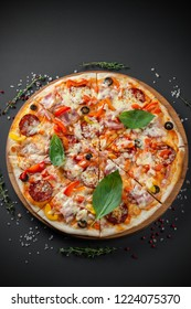Pizza with sausage and Basil on dark background