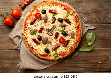 Pizza with sausage and mushrooms top view on wood