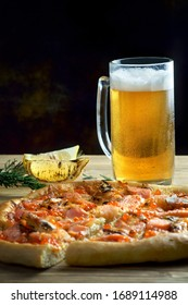 pizza with seafood and a glass of light beer