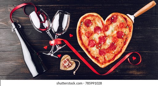 pizza in the shape of heart and wine with glasses tied with ribbon with hearts. on a dark wooden background.
