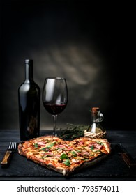 Pizza in the shape of heart with wine for St. Valentine's Day