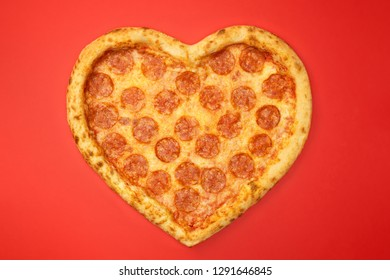 Pizza shaped heart top view Valentine's Day on red background.