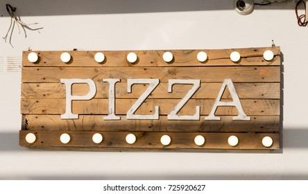 Pizza sign made of wooden planks and light bulbs on top and bottom