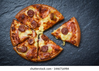 Pizza slice on dark background / delicious tasty fast food italian traditional pizza cheese with Mozzarella , Smoked pork sausage , Pineapple ham on topping sauce