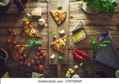 Pizza slice on wood with ingredients. Pizza with cheese, tomatoes and basil. Rustic italian pizza
