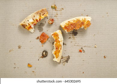 Pizza slices and crumbs in a pizza delivery box