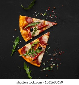 Pizza slices with rocket salad on black background, top view