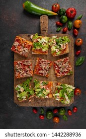 Pizza slices with shrimps, lettuce, tomato, tuna and onions, on a wood kitchen board, top view shot.