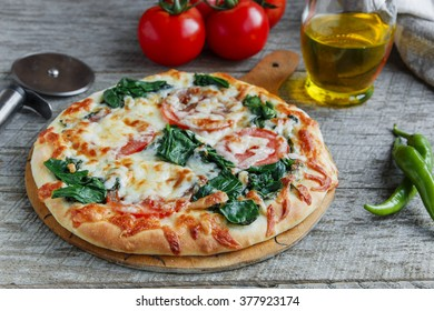 pizza with spinach tomato and cheese on a wooden surface