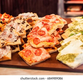 Pizza Take Away pieces on a stall in cafe, Traditional Italian Focaccia with tomatoes, black olives and cheese