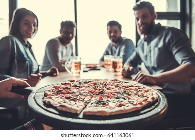 Pizza time. Close-up of tasty pizza on the table, with a group of young smiling people resting in the pub.