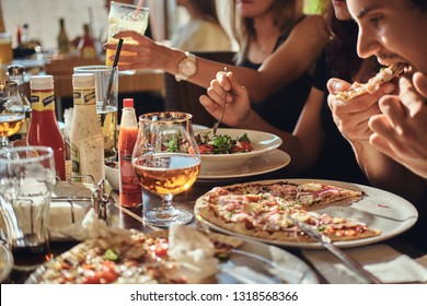 Pizza time. Young friends students eat pizza and salads in an outdoor caf during lunch break