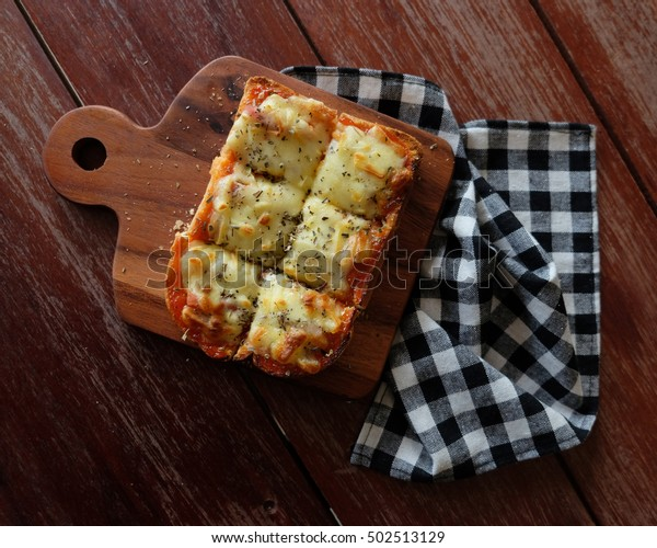 Pizza toasted bread with tomato sauce and ham cheese selective focus, picture vintage style