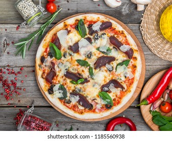 Pizza with tomatoes, mozzarella cheese, black olives and basil. Delicious italian pizza on wooden pizza board. Table top view