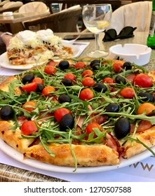 Pizza toscana with rucola and olives