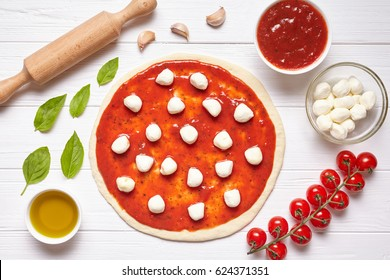 Pizza traditional preparation. Ingredients on the kitchen table: rolled dough with tomatoes sauce, basil, olive oil, mozzarella cheese, spices. Italian food cuisine background pizza margherita
