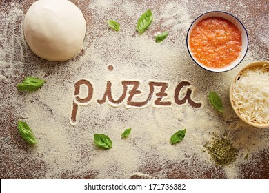 Pizza word written on table composition with ingredients