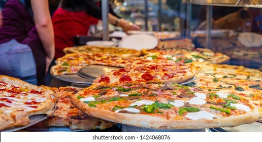 Pizzeria glass window. Variety of italian pizzas in a shop display, street food. Kitchen workers arranging the pizzas.