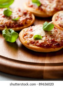 Pizzete. Home baked mini pizzas with fresh basil on wooden background. Italian cuisine. Symbolic image. Concept for a tasty vegetarian meal. Selective focus. Close up.