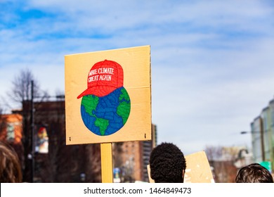 Placard by ecological protestor at rally. A closeup view of a cardboard sign with a picture of planet earth wearing Trumps cap saying make climate great again, as eco campaigners march for environment