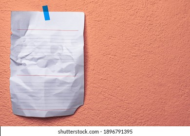 Place an ad on the orange rough wall. A piece of paper is taped together. Orange design background. The adhesive tape holds a sheet of paper on the wall.