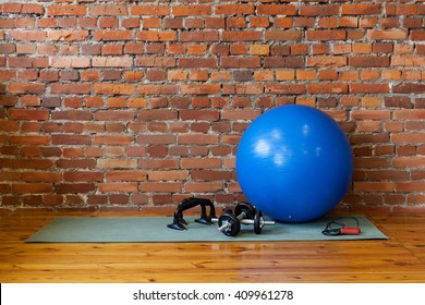 Place for fitness and exercise. The mat, fitball, rope, dumbbells and stand push-ups lie on the floor in the gym.